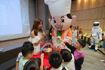 Photo shows staff explaining Master Kong's space Instant noodles to the younger generation.