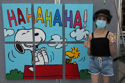 """Tools of the Happiness Trade, Peanuts-Style: At The Children's Hospital at Westmead in Sydney, Australia, patient Bella Conciatore celebrates the new Snoopy and Woodstock mural she helped paint, which will hang in the hospital as a gift from Peanuts Worldwide and the nonprofit Foundation for Hospital Art. The mural is one of 70 being donated to hospitals worldwide as part of the global """"Take Care With Peanuts"""" initiative, launched October 2 in conjunction with the 70th Anniversary of Peanuts."""