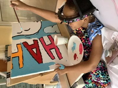"""Flying High with Woodstock: Young patient Za'Nii Roundtree shows off her awesome painting skills as she contributes to a new Snoopy and Woodstock mural at Gillette Children's in St. Paul, Minnesota—hometown of Peanuts creator Charles Schulz. The mural is one of 70 being donated to hospitals worldwide by Peanuts Worldwide and the nonprofit Foundation for Hospital Art as part of the global """"Take Care With Peanuts"""" initiative, launched October 2in conjunction with the 70th Anniversary of Peanuts"""