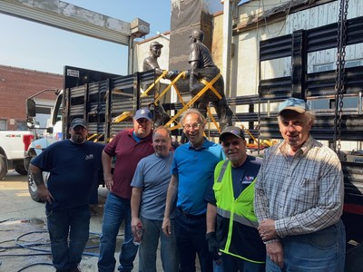 """The Aim driving team secures the statue in Brooklyn, NY, with the help of members of the Robinson-Shuba """"bullpen,"""" including sculptor Marc Mellon (pictured middle, in the light-blue polo)."""
